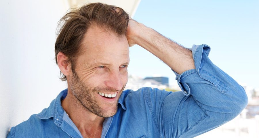 close up attractive male model smiling with hand i 74X9QCB
