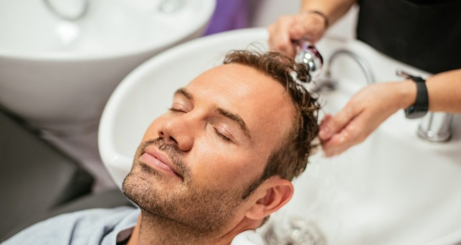 man having his hair washed in a barbershop 5ZT7DW4